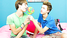 Two young twinks are share licking one candy